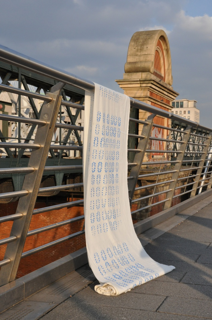 Fabric hang from hand rail along Hungerford Bridge