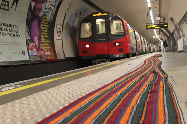 Fabric spread along London Undergrounds platform with train pulling in.